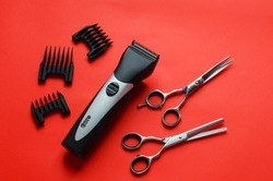 Barber clipper,scissors for haircuts,nozzles for haircuts on a red background.Free space for text.Barber tool.New year at the hairdresser.Discounts and promotions for the new year.New Years hairstyles