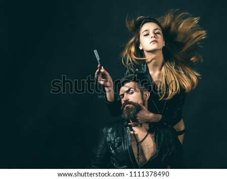 Barber concept. Couple of sexy girl and brutal bearded hipster with mustache, black background. Barber with straight razor works on haircut. Hipster with beard and sexy girl holds straight razor.