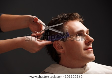 Barber cutting hair with scissors and comb, a client is a young caucasian man