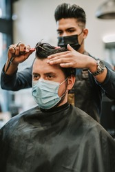 Barber giving a haircut. Barber wearing mask. Customer wearing mask at barbershop. Working and safety during COVID-19.