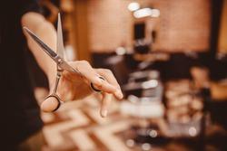 Barber hairdresser holds scissors on background chair, beauty salon for men.