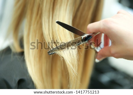 barber hand cuts hair close up. barber hand holds thinning shears