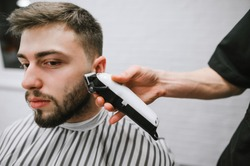 Barber hand with a clipper cuts hair of an, bearded man, close portrait of a client receives service of a male hairdresser in a barber shop. Barber job concept. Hairdressing in a hairdresser.