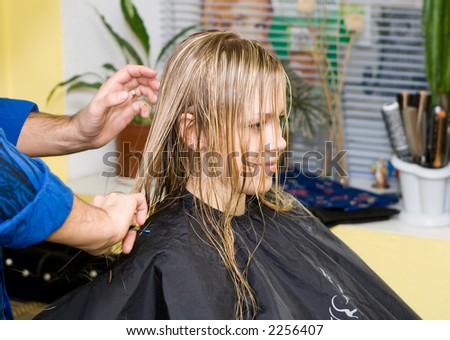 Barber makes a hair-dress to the young blonde - stock photo