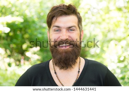 Barber obsessing about his hair. Bearded man with shaped beard and mustache hair smiling before or after visiting barber. Happy barber on natural landscape. A barber shop for men only.