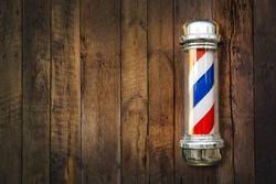 Barber pole. Barbershop pole on a wooden background with copy space.