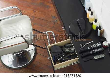 Barber\'s chair beside open draw of hair products, scissors and hairbrushes in salon, overhead view