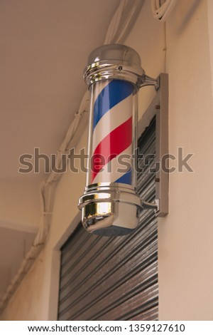 Barber's pole of white and red colors, anchored to the wall of the barbershop or village barbershop