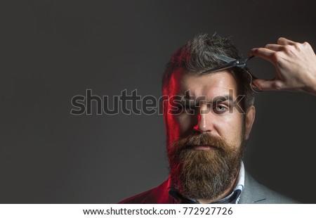 Barber scissors. Bearded man, lush beard, handsome. Hipster in barbershop. Mens haircut in barber shop. Vintage barbershop, shaving. Bearded male, long beard, brutal, caucasian male with moustache.