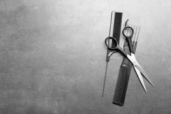 Barber set with two combs and scissors on grey background