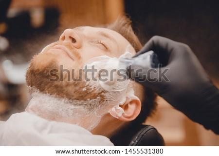 Barber shaves beard of man in barbershop with razor.