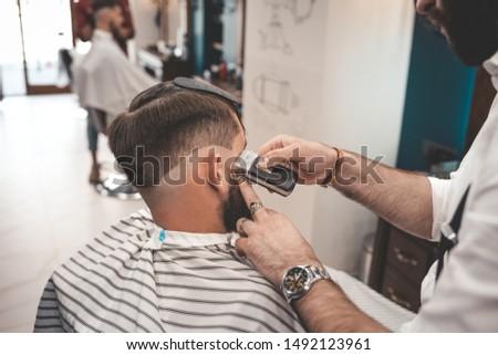 Barber shaves client in barbershop. Barbershop concept