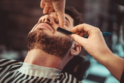 Barber shaving a bearded man in a barber shop, close-up