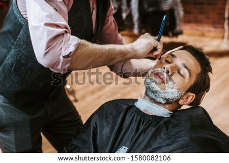 barber shaving handsome man with shaving cream on face