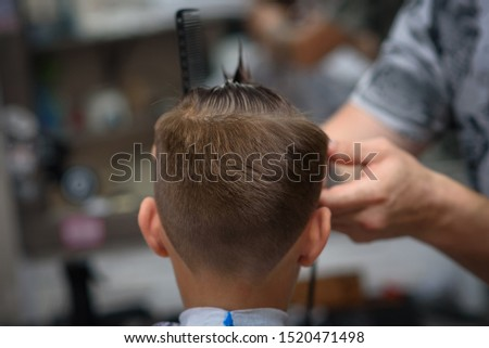 Barber shop. Barber makes hairstyle to a boy with styling gel and hairbrush.