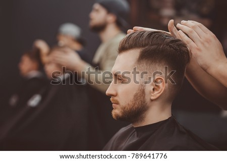 Barber shop. Man in barber's chair, hairdresser styling his hair