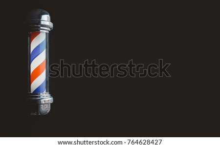 Barber shop pole baner at entrance of the window. background is dark. copyspace