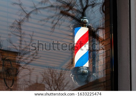 Barber shop pole seen in the barber shop window. barber culture concept. Barber shop pole by the entrance