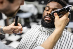 Barber trim hair with clipper on young unshaven black man in barbershop studio.Professional hairdresser cut hair with electric shearer machine on African guy.