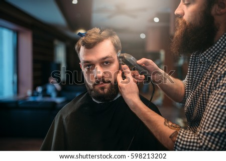 Barber trimming hair of the client man by clipper #598213202