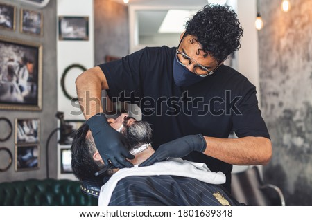 barber with a protection mask shaving a client with a razor Photo stock ©