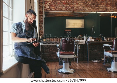 Barber with digital tablet sitting on window sill of salon. Hairdresser organizing his business using latest technology.