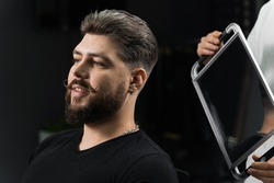 Barber with dreadlocks showing result of low fade machine hair and beard cut for bearded man in barbershop. Hairstyle with a smooth transition