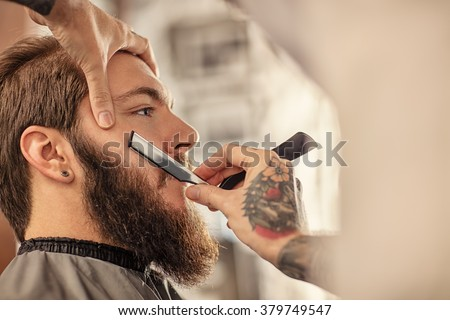 Barber with old-fashioned black razor shaving bearded man