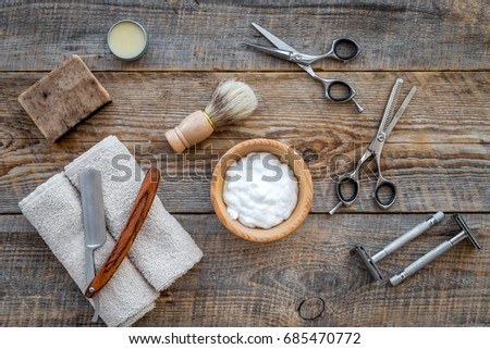 Barber workplace. Shaving brush, razor, foam, sciccors on wooden table background top view