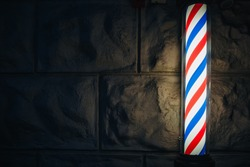 Barbers pole with red, blue and white turning spiral. Temporarily closed, lockdown. Barber shop pole turning at night. Barber's Pole.