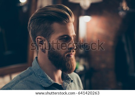 Shutterstock Barbershop concept. Profile side portrait of attractive severe brutal red bearded young guy. He has a perfect hairstyle, modern stylish haircut