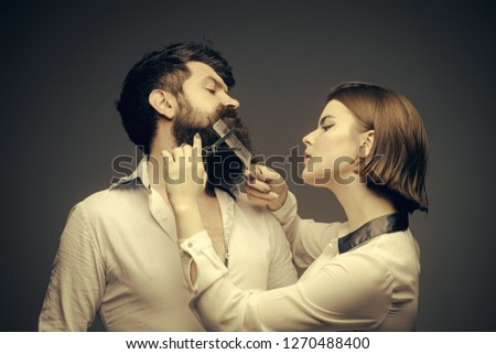 Barbershop or hairdresser concept. Woman hairdresser cuts beard with scissors. Man with long beard, mustache and stylish hair, grey background. Guy with modern hairstyle visiting hairdresser
