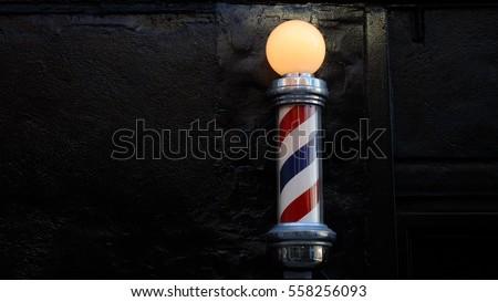 Barbershop pole against black brick wall.