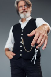 Barbershop tools. Against grey background. Stylish modern senior man with gray hair and beard is indoors.