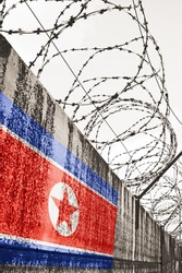 Barbwire and grey wall with North Korea national flag