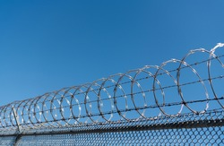barbwire perimeter fence. ensuring safety and security. jail wall.