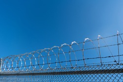 barbwire prison wall with barbed wire fence coiled razor wire perimeter fence, barbed fence.