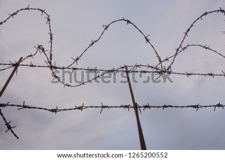Barbwire silhouette with a cloudy background a gloomy sky and gloomy day  #1265200552