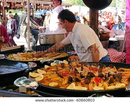 "BARCELONA - APRIL 30: ""April fair in Barcelona - 2009"" lasts 5 days. Cook from Valencia prepares  national dish  paella and  fried potato. April, 30, 2009, Barcelona - stock photo"