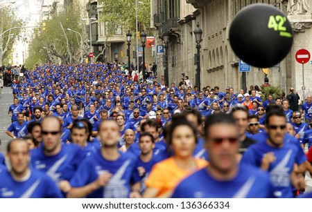 BARCELONA - APRIL, 21: Barcelona street crowded of athletes running during Bombers Race in Barcelona April 21, 2013 in Barcelona, Spain