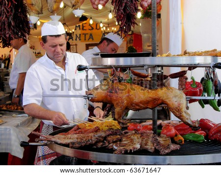 BARCELONA - APRIL 30: Cooks from Valencia fries on a barbecue of a pig and vegetables during April fair on April, 30, 2009 in Barcelona, Spain, Catalonia