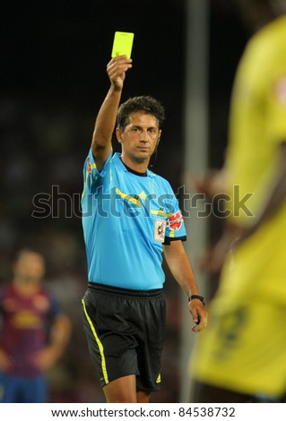BARCELONA - AUG,29: Referee Turienzo Alvarez delivers yellow card during a Spanish League match between FC Barcelona vs CF Villarreal at the Nou Camp Stadium on August 29, 2011 in Barcelona, Spain