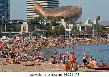 BARCELONA - AUGUST 14: Barceloneta Beach with Frank Gehry's Peix d'Or (Whale Sculpture) on the beach of Barceloneta on August 14, 2009 in Barcelona, Spain.
