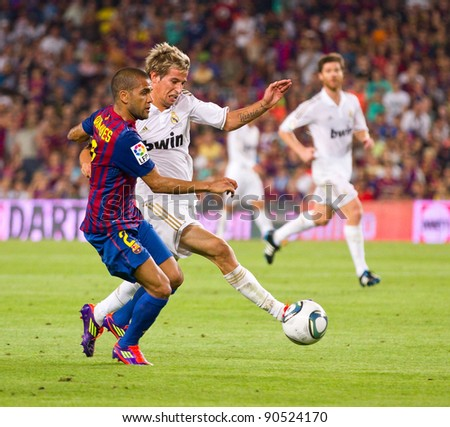 BARCELONA - AUGUST 17: Dani Alves (L) and Fabio Coentrao (R) in action during the Spanish Super Cup final match between FC Barcelona and Real Madrid, 3 - 2, on August 17, 2011 in Barcelona, Spain.