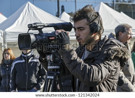 BARCELONA - DECEMBER 09: Cameraman TV covering the news of exhibition during the Montjuic Revival 2012. Barcelona Spain, December 09, 2012