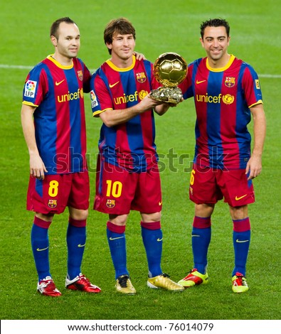 BARCELONA - JANUARY 12: Andres Iniesta, Leo Messi and Xavi Hernandez offering the FIFA World Player Award to the Barcelona soccer supporters.  January 12, 2011 in Nou Camp stadium, Barcelona, Spain. - stock photo
