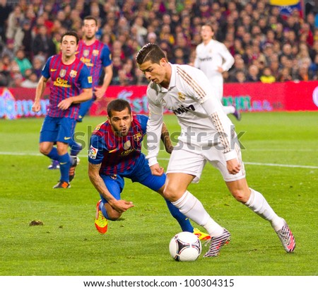 BARCELONA - JANUARY 25: Dani Alves and Cristiano Ronaldo (R) in action during the Spanish Cup match between FC Barcelona and Real Madrid, final score 2 - 2, on January 25, 2012, in Barcelona, Spain.