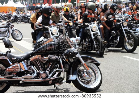 BARCELONA - JULY 10: Harley-Davidson Motorcycles parked with some unidentified people over their bikes during the Barcelona Harley Days event on the city streets on July 10, 2011 in Barcelona, Spain