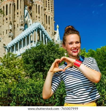 Barcelona - July, 10, 2017: modern tourist woman in yellow shorts and stripy shirt in Barcelona, Spain showing heart shaped hands #765007999