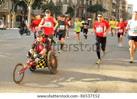 BARCELONA - MARCH 3: An unidentified athlete with mobility disabilities participates with other athletes during Barcelona Marathon on March 3, 2011 in Barcelona, Spain